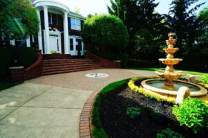 front of large brick home with a fountain in middle of landscape