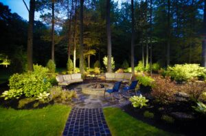 stone patio with inground fire pit and outdoor lighting on surrounding trees