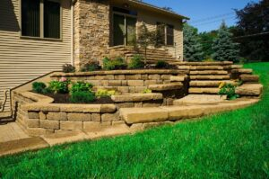 stone patio with stairs and plants along wall